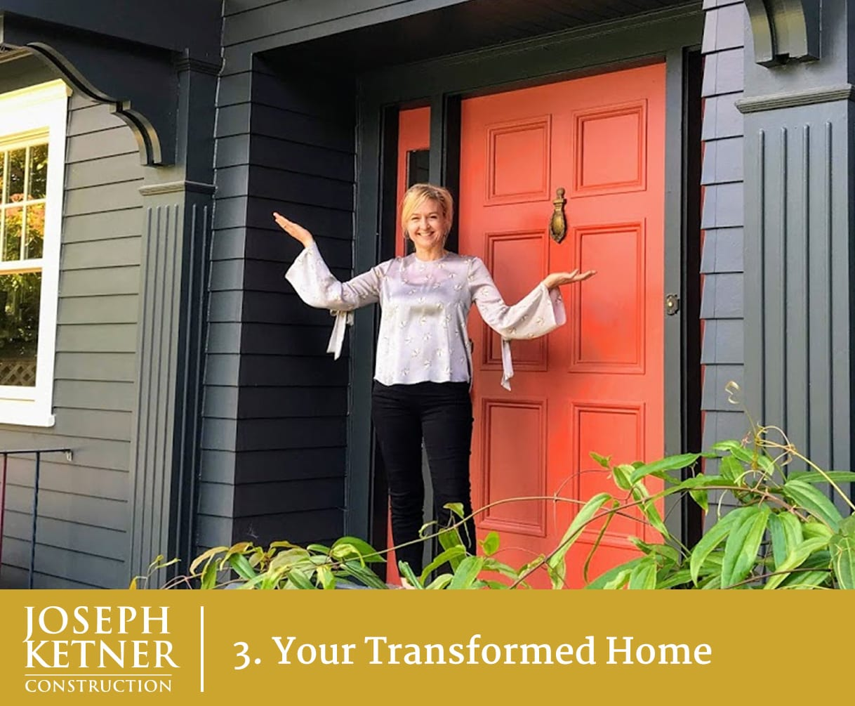 A happy female home owner standing in front of a red front door